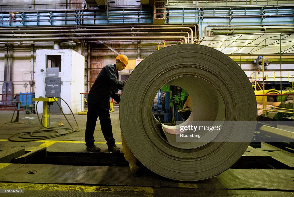 A worker inspects a drum of steel sheeting as it is moved along the production line at OAO Mechel's metallurgical plant in Chelyabinsk, Russia, on Wednesday, July 17, 2013. Mechel, the country's largest producer of coking coal for steelmakers has begun operating its $700m rail production line which can produce 100 meter rails. Photographer: Andrey Rudakov/Bloomberg via Getty Images