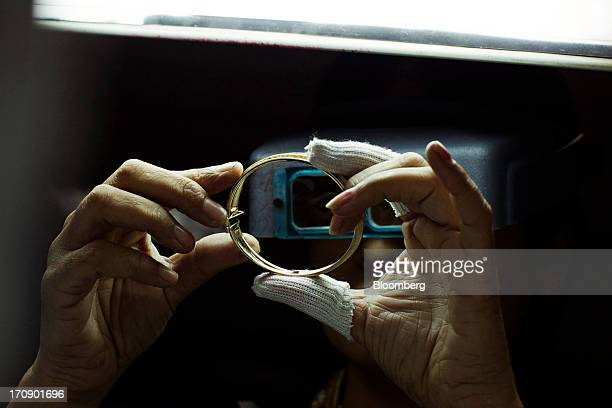 A worker inspects a gold bangle through magnifying goggles at the Kama Schachter Jewelry Pvt Ltd diamond studded gold and platinum manufacturing...