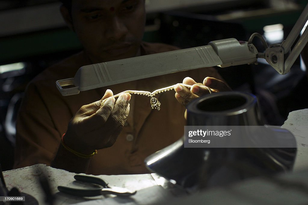 A worker inspects a necklace in the assembly unit of the Kama Schachter Jewelry Pvt Ltd. diamond studded gold and platinum manufacturing facility in Mumbai, India, on Wednesday, June 19, 2013. India's exports of diamonds and gold jewelry grew 5.2% to $6.1 billion in April and May, says the Gem & Jewellery Export Promotion Council on June 18, 2013. Photographer: Adeel Halim/Bloomberg via Getty Images