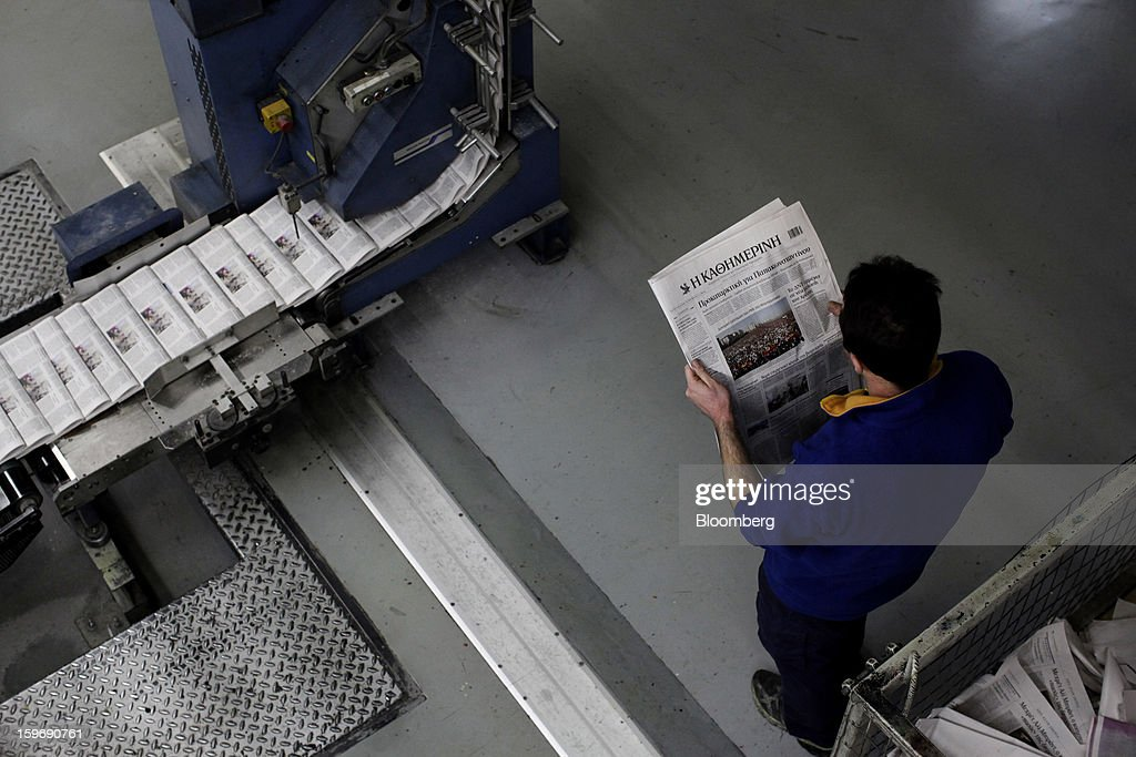 A worker inspects a newly-printed edition of the Kathimerini newspaper near the automated production line at the Kathimerini printing plant in Paiania, Greece, on Thursday, Jan. 17, 2013. An anarchist group claimed responsibility for a series of attacks early on Jan. 11 when unidentified perpetrators threw makeshift bombs made from propane gas canisters into the homes of five Greek journalists working for national media saying it was to protest coverage of the country's financial crisis seen as sympathetic to the government. Photographer: Kostas Tsironis/Bloomberg via Getty Images