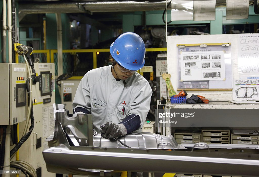A worker inspects a part of a minicar which will be sold as the Nissan DAYZ by Nissan Motor Co. and Mitsubishi eK Wagon by Mitsubishi Motors Corp. on the production line of the Mitsubishi Motors Mizushima plant in Kurashiki City, Okayama Prefecture, Japan, on Monday, May 20, 2013. Nissan will start selling the first minicar it jointly developed with Mitsubishi Motors in Japan next month amid increasing demand from the nation's consumers for smaller and cheaper vehicles. Photographer: Tomohiro Ohsumi/Bloomberg via Getty Images