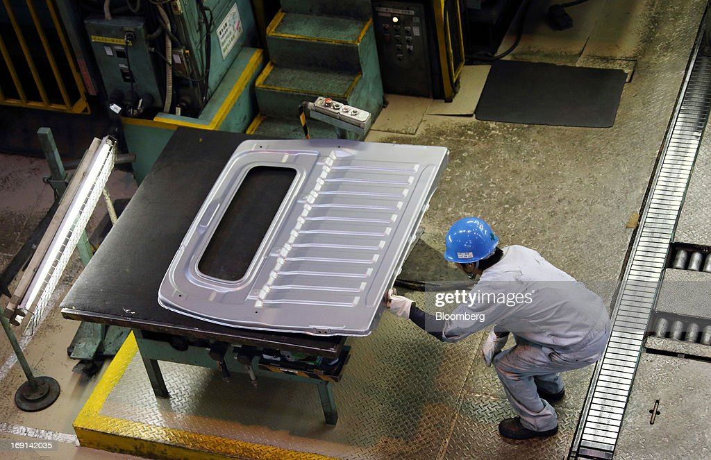 A worker inspects a section of a minicar which will be sold as the Nissan DAYZ by Nissan Motor Co. and Mitsubishi eK Wagon by Mitsubishi Motors Corp. on the production line of the Mitsubishi Motors Mizushima plant in Kurashiki City, Okayama Prefecture, Japan, on Monday, May 20, 2013. Nissan will start selling the first minicar it jointly developed with Mitsubishi Motors in Japan next month amid increasing demand from the nation's consumers for smaller and cheaper vehicles. Photographer: Tomohiro Ohsumi/Bloomberg via Getty Images