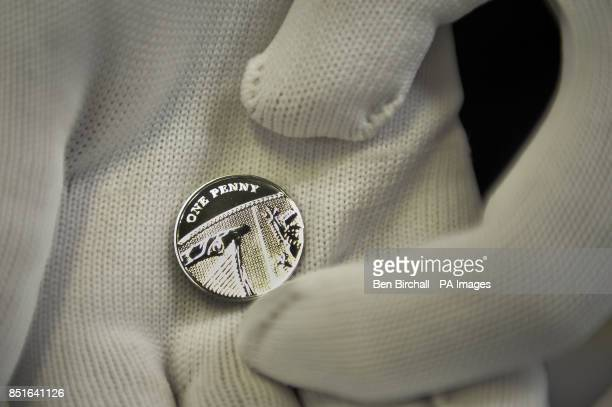 A worker inspects a Silver Penny produced by the Royal Mint to coincide with the brith of the royal baby