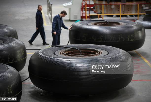 A worker inspects a super oversized rubber tire at the Belshina JSC tire factory in Babruysk Belarus on Thursday March 16 2017 Belshina Belarus...