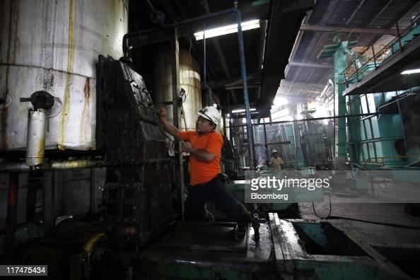 A worker inspects a tank at the PT Perkebunan Nusantara VIII plantation and production factory in Kertajaya Banten Province Indonesia on Monday June...