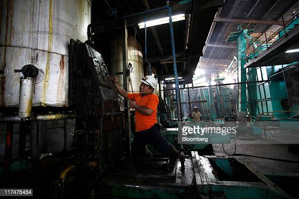 A worker inspects a tank at the PT Perkebunan Nusantara VIII plantation and production factory in Kertajaya Banten Province Indonesia on Monday June...