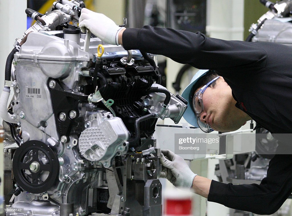 A worker inspects an engine for the Toyota Motor Corp. Aqua hybrid compact car on the production line of Toyota Motor East Japan Inc.'s Miyagi Taiwa Plant in Taiwa, Miyagi Prefecture, Japan, on Friday, Dec. 14, 2012. Toyota Motor East Japan Inc. commenced operations at the plant today. Photographer: Tomohiro Ohsumi/Bloomberg via Getty Images