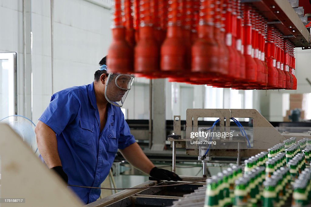 A worker inspects bottles of beer moving along a production line at the Jinzhu Manjiang beer factory on August 1, 2013 in Fujin, Heilongjiang Province, China. Recent significant sustained high temperatures in China are expected to push beer industry volume and revenue growth up significantly.