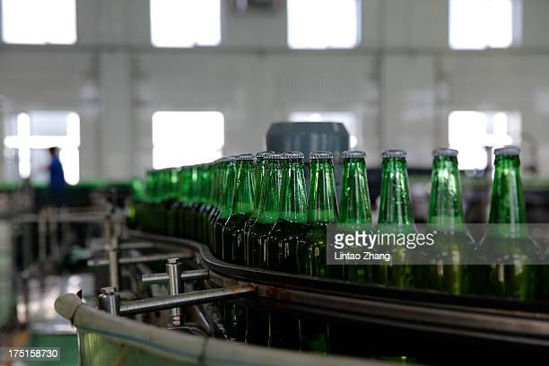 A worker inspects bottles of beer moving along a production line at the Jinzhu Manjiang beer factory on August 1 2013 in Fujin Heilongjiang Province...
