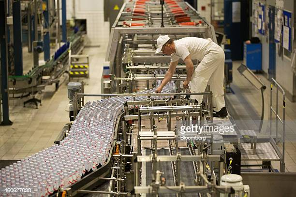 A worker inspects bottles of Kronenbourg 1664 Blanc beer as they move along the production line at the OAO Baltika brewery operated by Carlsberg A/S...