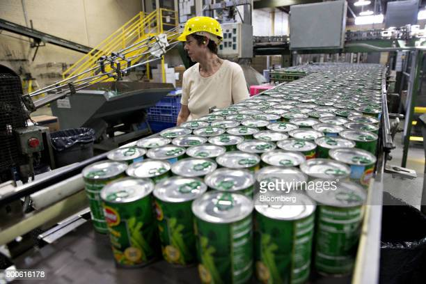 A worker inspects cans of peas and carrots as they move along a conveyor at the Del Monte Foods Inc facility in Mendota Illinois US on Friday June 23...
