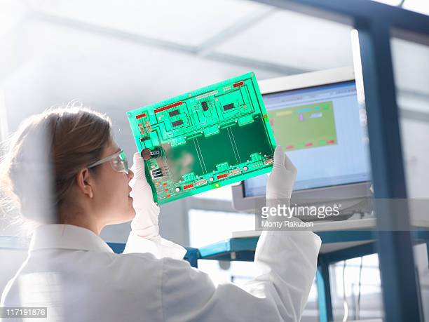 Worker inspects circuit board