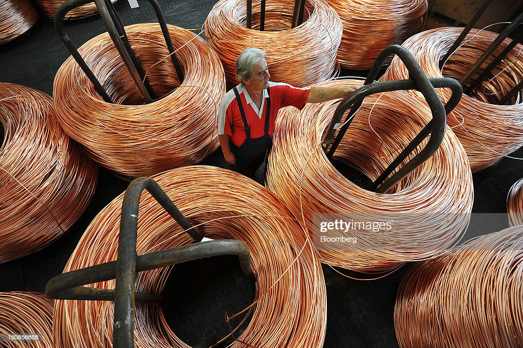 A worker inspects coiled bundles of 8mm copper wire before shipping in a warehouse at the copper mining and smelting complex, operated by RTB Bor Group, in Bor, Serbia, on Friday, Aug. 24, 2012. Copper neared a one-week low in London on signs Asian economies are slowing and speculation that U.S. policy makers will refrain from a fresh round of stimulus. Photographer: Oliver Bunic/Bloomberg via Getty Images