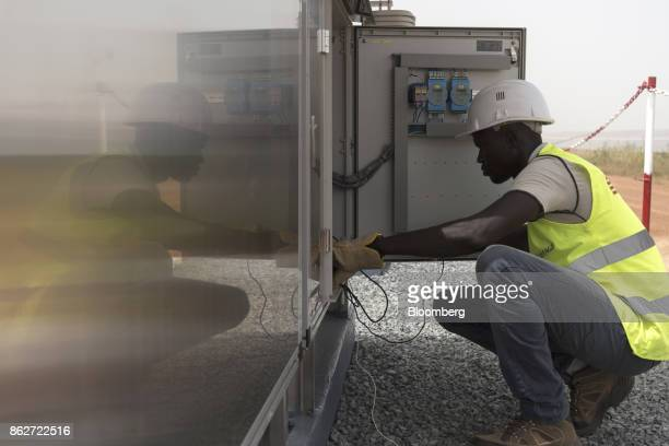 A worker inspects connections inside a control box at the Senergy Santhiou Mekhe PV solar plant in Thies Senegal on Monday Oct 16 2017 The...