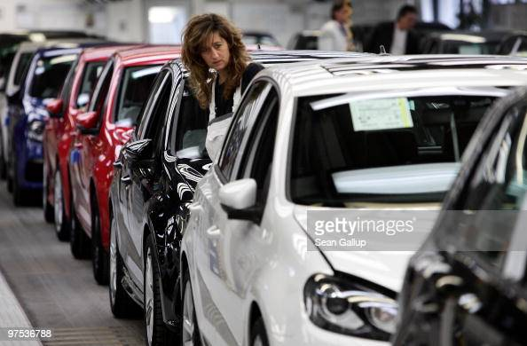 A worker inspects finsihed Volkswagen Golf cars at the end of the assembly line at the VW factory on March 8 2010 in Wolfsburg Germany Volkswagen...