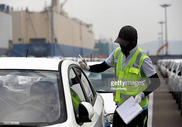 A worker inspects Kia Motors Corp vehicles bound for export at the port of Pyeongtaek South Korea on Thursday Aug 9 2012 South Korea's gross domestic...