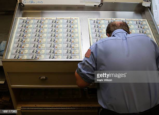 A worker inspects newly redesigned $100 notes during the printing process at the Bureau of Engraving and Printing on May 20 2013 in Washington DC The...
