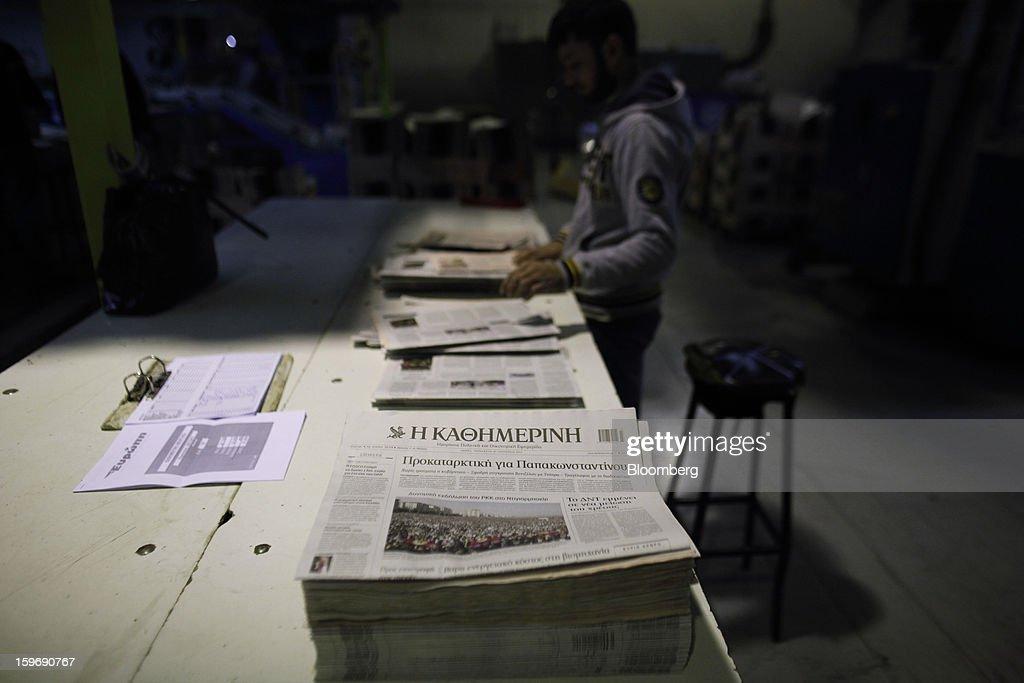 A worker inspects newly-printed copies of the Kathimerini newspaper at the Kathimerini printing plant in Paiania, Greece, on Thursday, Jan. 17, 2013. An anarchist group claimed responsibility for a series of attacks early on Jan. 11 when unidentified perpetrators threw makeshift bombs made from propane gas canisters into the homes of five Greek journalists working for national media saying it was to protest coverage of the country's financial crisis seen as sympathetic to the government. Photographer: Kostas Tsironis/Bloomberg via Getty Images