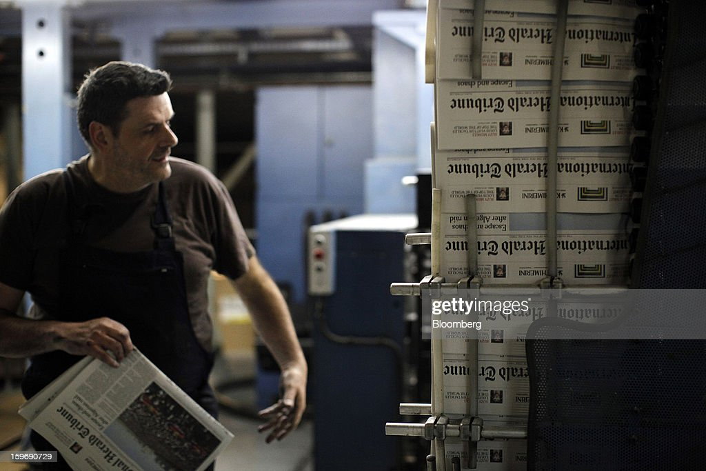 A worker inspects newly-printed editions of the International Herald Tribune newspaper at the Kathimerini printing plant in Paiania, Greece, on Thursday, Jan. 17, 2013. An anarchist group claimed responsibility for a series of attacks early on Jan. 11 when unidentified perpetrators threw makeshift bombs made from propane gas canisters into the homes of five Greek journalists working for national media saying it was to protest coverage of the country's financial crisis seen as sympathetic to the government. Photographer: Kostas Tsironis/Bloomberg via Getty Images