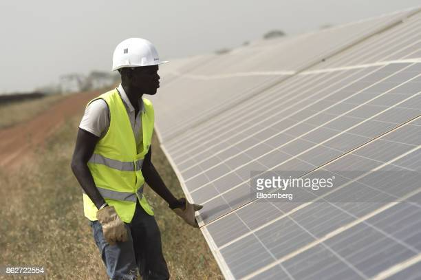 A worker inspects photovoltaic solar panels in an array at the Senergy Santhiou Mekhe PV solar plant in Thies Senegal on Monday Oct 16 2017 The...