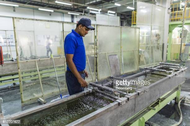 A worker inspects plastic threads passing through an extruder that makes pellets at Dainichi Color India Pvt's factory in the Rajasthan State...