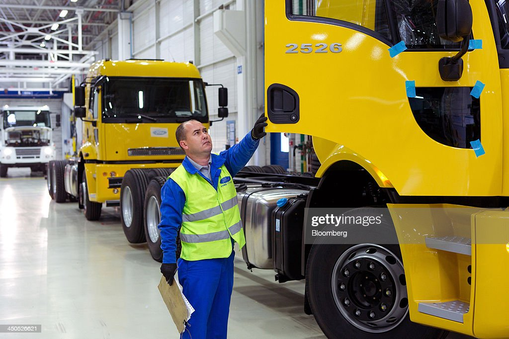 A worker inspects the driver's cabin door of a Ford Cargo truck nearing completion on the production line at Ford Otosan, the joint venture between Ford Motor Co.'s Ford Otomotiv Sanayi AS and Koc Holding AS, in Eskisehir, Turkey, on Monday, Nov. 18, 2014. Ford Otomotiv Sanayi AS chief executive officer Haydar Yenigun said in September Turkey is about to 'lose the diamond' which is light commercial vehicle production due to government policies such as tax hikes, ban on their lease, Dunya newspaper says. Photographer: Kerem Uzel/Bloomberg via Getty Images