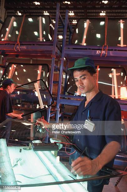 A worker inspects the electrical heating element on a rear windscreen at the Siam VMC Safety Glass Company The company specialises in manufacturing...