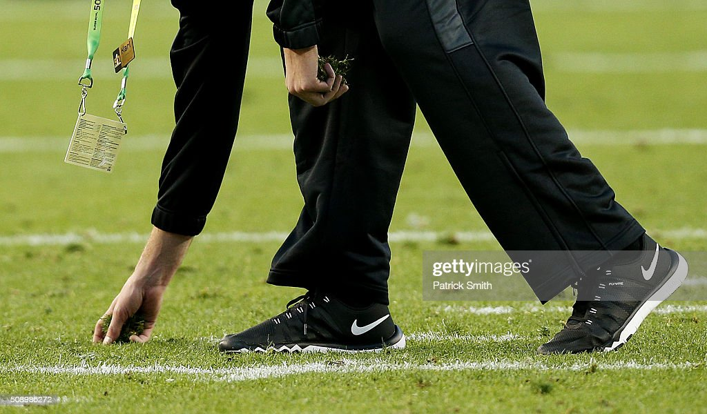 A worker inspects the field turf during Super Bowl 50 between the Denver Broncos and the Carolina Panthers at Levi's Stadium on February 7 2016 in...
