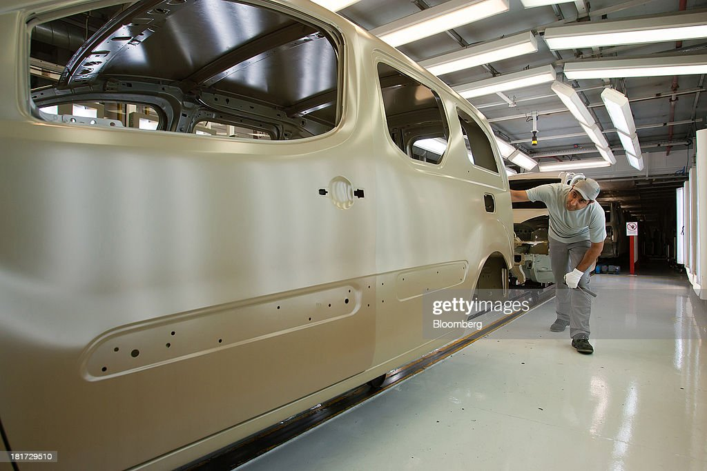 A worker inspects the paintwork of a Citroen Berlingo automobile at the PSA Peugeot Citroen production plant in Mangualde, Portugal, on Monday, Sept. 23, 2013. Some economists point to falling labor costs across southern Europe as a sign the region may be becoming more attractive as a manufacturing base. Photographer: Mario Proenca/Bloomberg via Getty Images