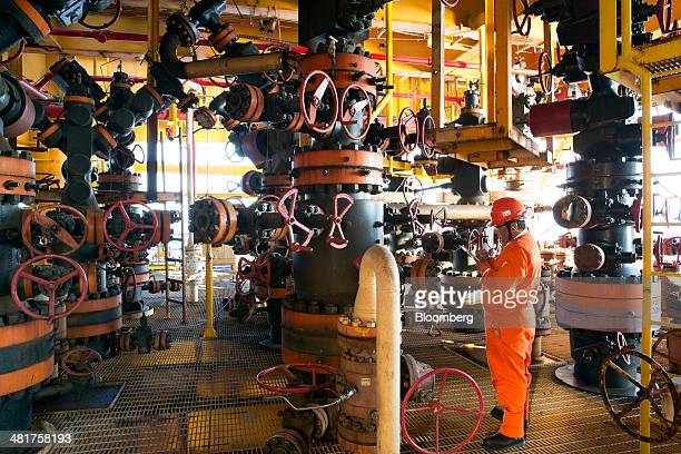 A worker inspects the pressure of the valves in a section of the Petroleos Mexicanos PolA Platform complex located on the continental shelf in the...