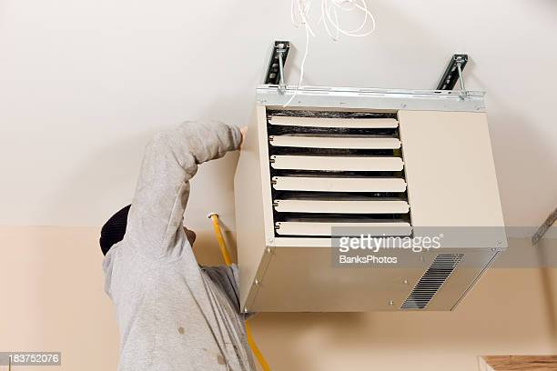 Worker Installing Ceiling Mounted Gas Heater