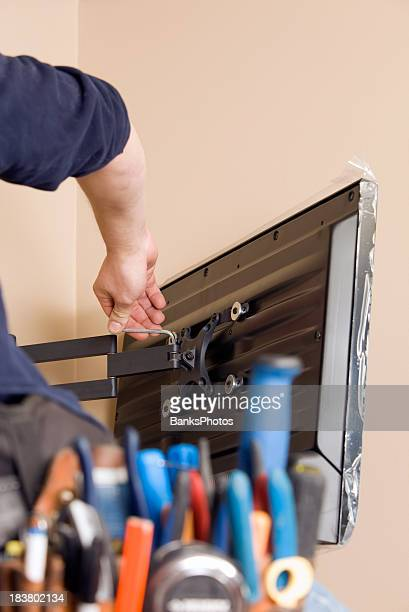 Worker Installing New TV with Tool Belt Foreground