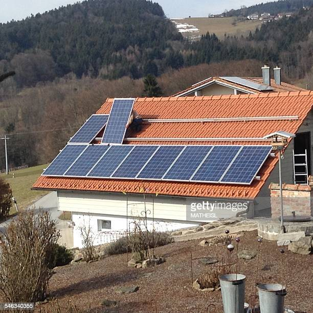 Worker Installing Solar Panels on Tiled Roof Bavaria Germany Europe March 2015
