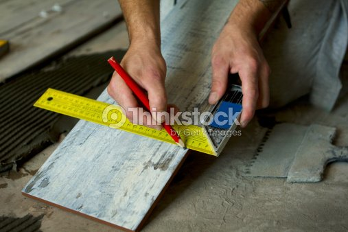 Worker Installing Tiles On The Floor Measurement Of Ceramic Tile