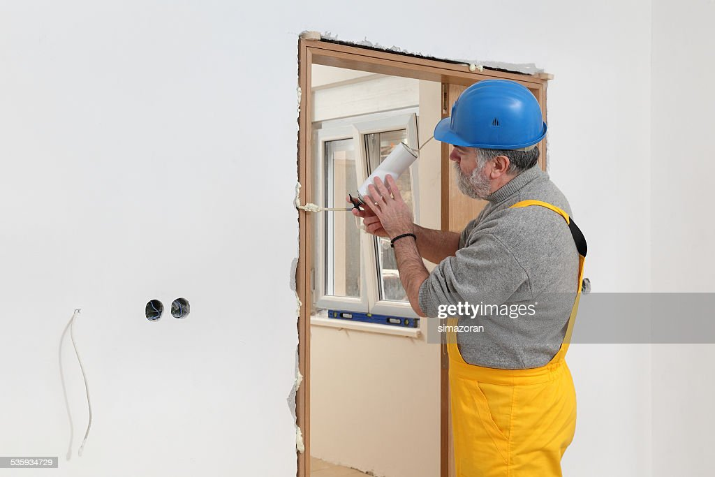 Worker installing wooden door, using polyurethane foam : Stock Photo