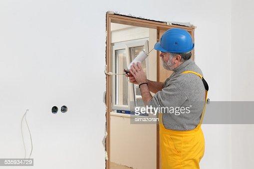 Worker installing wooden door, using polyurethane foam : Stock Photo