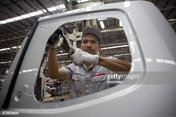 A worker installs a component onto a door panel of a Nissan Motor Co Navara pickup truck on an assembly line at the company's plant in Samut Prakan...