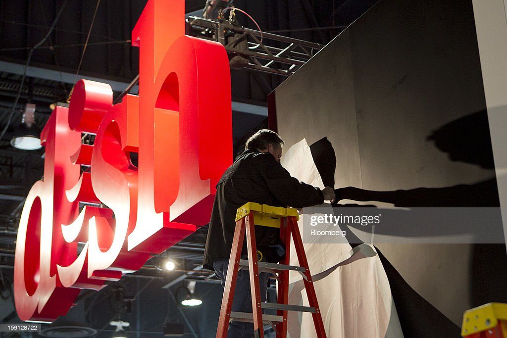A worker installs a display at the Dish Network booth during the 2013 Consumer Electronics Show in Las Vegas, Nevada, U.S., on Tuesday, Jan. 8, 2013. The 2013 CES trade show, which runs until Jan. 11, is the world's largest annual innovation event that offers an array of entrepreneur focused exhibits, events and conference sessions for technology entrepreneurs. Photographer: Andrew Harrer/Bloomberg via Getty Images