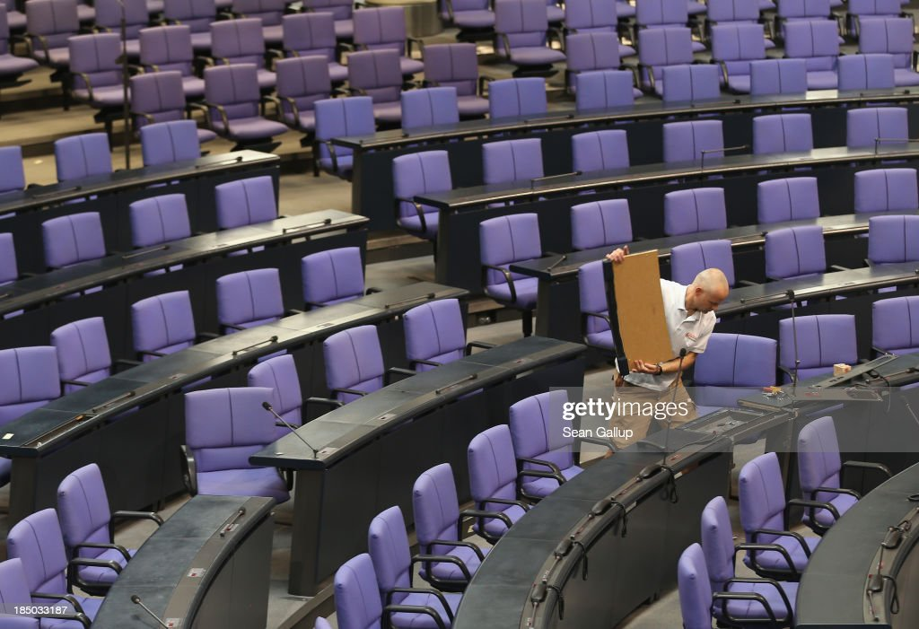 A worker installs a new desk and chair in the plenary hall of the Bundestag on October 17, 2013 in Berlin, Germany. Workers installed new chairs and rearranged seating in order to accomodate the new constellation of party factions as well as the slightly higher number of parliamentarians voted in for the 18th legislative period following recent German elections. The new Bundestag will convene for th first time on October 22.