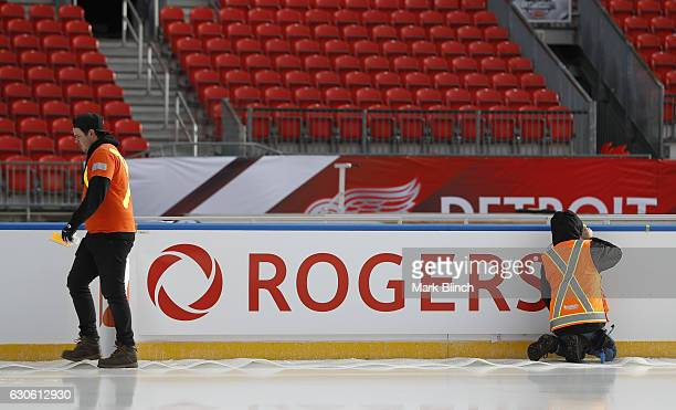 A worker installs a 'Rogers' advertisement on the boards during the build out of the outdoor rink for the 2017 Scotiabank NHL Centennial Classic...