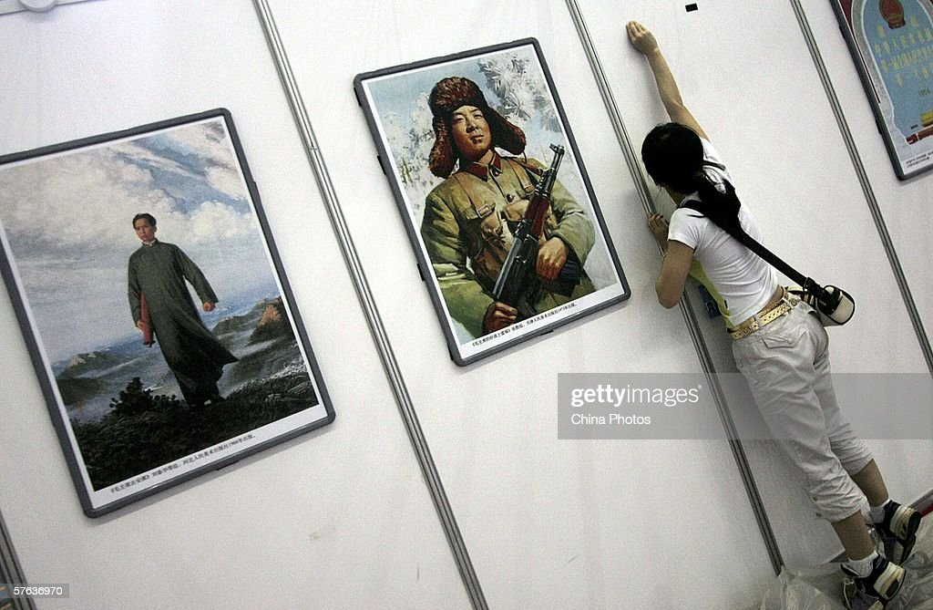 A worker installs an exhibit area beside a picture poster of Lei Feng, a soldier who became China's symbol of sacrifice for others, at the 2006 China (Shenzhen) International Cultural Industry Fair (ICIF) on May 17, 2006 in Shenzhen of Guangdong Province, China. ICIF, to be held from May 18 to 21, is China's only state-level exhibition on the cultural industry. According to state media, experts warned that the Chinese art market high might be about to end. China's art market boomed in recent years as art collection became a hot investment.