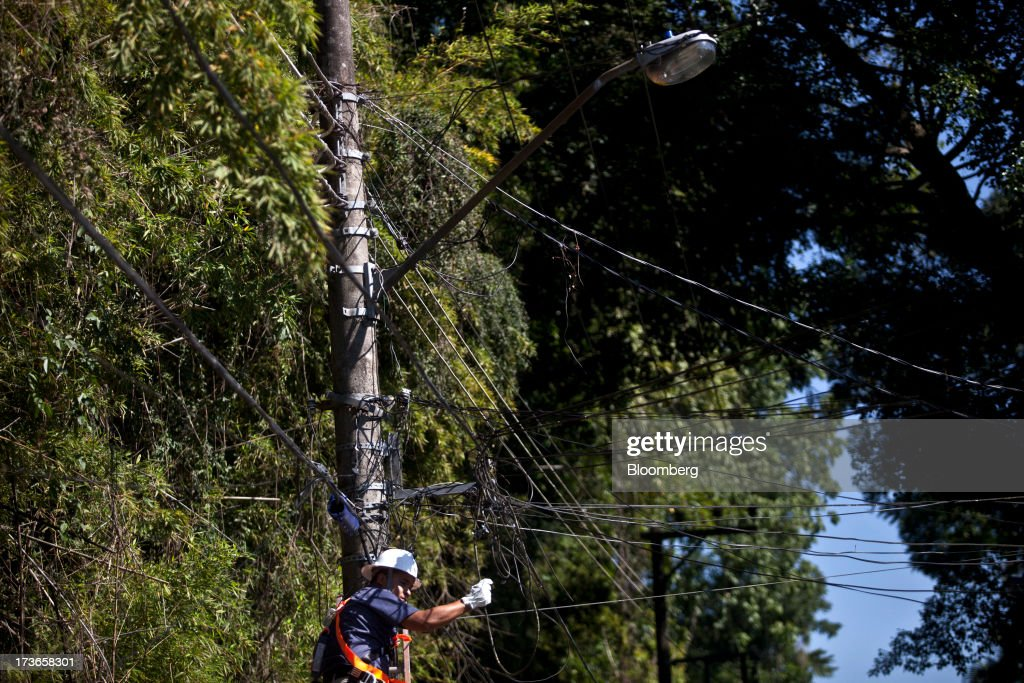 A worker installs cables on an electricity pole in the Santa Teresa neighborhood of Rio de Janeiro, Brazil, on Monday, July 15, 2013. Energy developers in Brazil will bid for contracts to sell electricity Dec. 13 from plants due to go into operation in five years, including a 700-megawatt hydropower project in the Amazon. Photographer: Dado Galdieri/Bloomberg via Getty Images