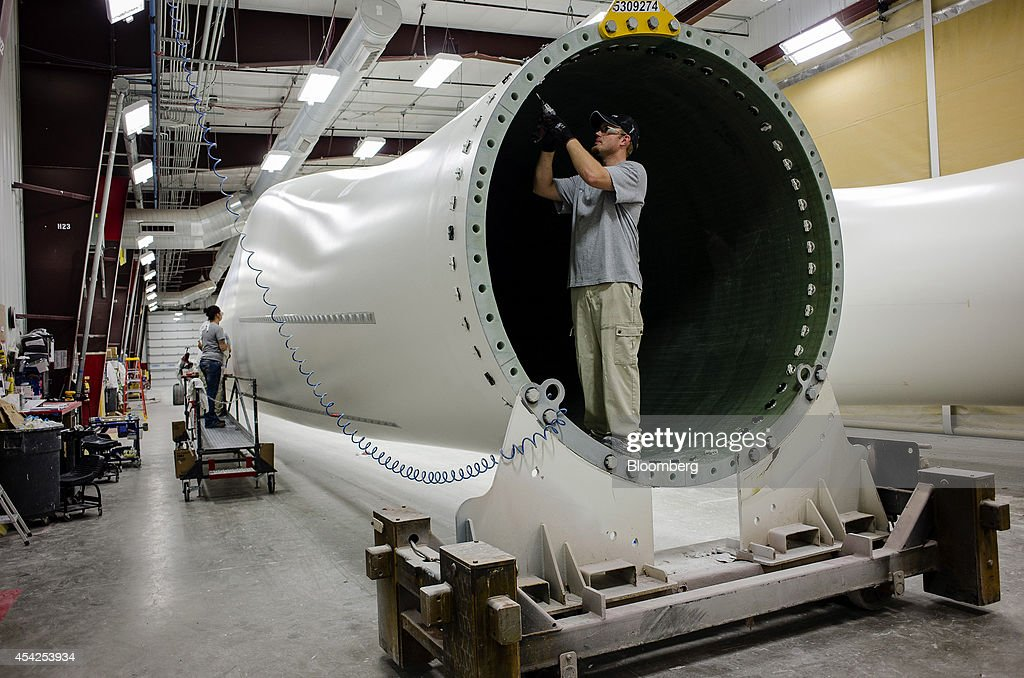 A worker installs components at the base of a wind turbine blade during the final phase of production at the Siemens AG turbine blade plant in Fort...