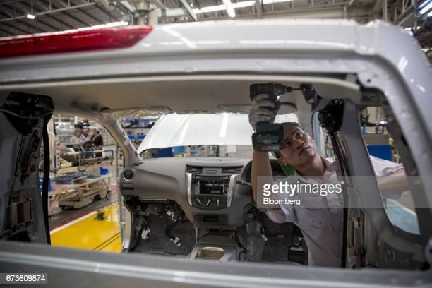 A worker installs components into a Nissan Motor Co Navara pickup truck on an assembly line at the company's plant in Samut Prakan Thailand on...