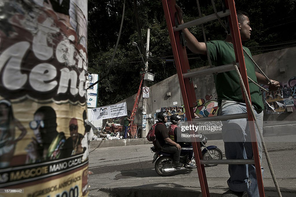 A worker installs fiber optic cables as motorists ride by on a scooter in the Rocinha slum of Rio de Janeiro, Brazil, on Wednesday, Nov. 28, 2012. About 56 percent of the 12 million people who live in slums like Rocinha were considered middle class in 2011, up from 29 percent in 2001, according to a study this year by Instituto Data Popular, a Sao Paulo-based research group. Photographer: Dado Galdieri/Bloomberg via Getty Images
