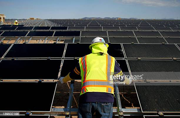 A worker installs First Solar Inc photovoltaic solar panels at the Agua Caliente Solar Project in Yuma County Arizona US on Wednesday Feb 16 2012...