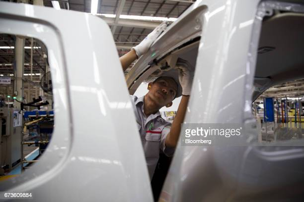 A worker installs interior components into a Nissan Motor Co Navara pickup truck on an assembly line at the company's plant in Samut Prakan Thailand...
