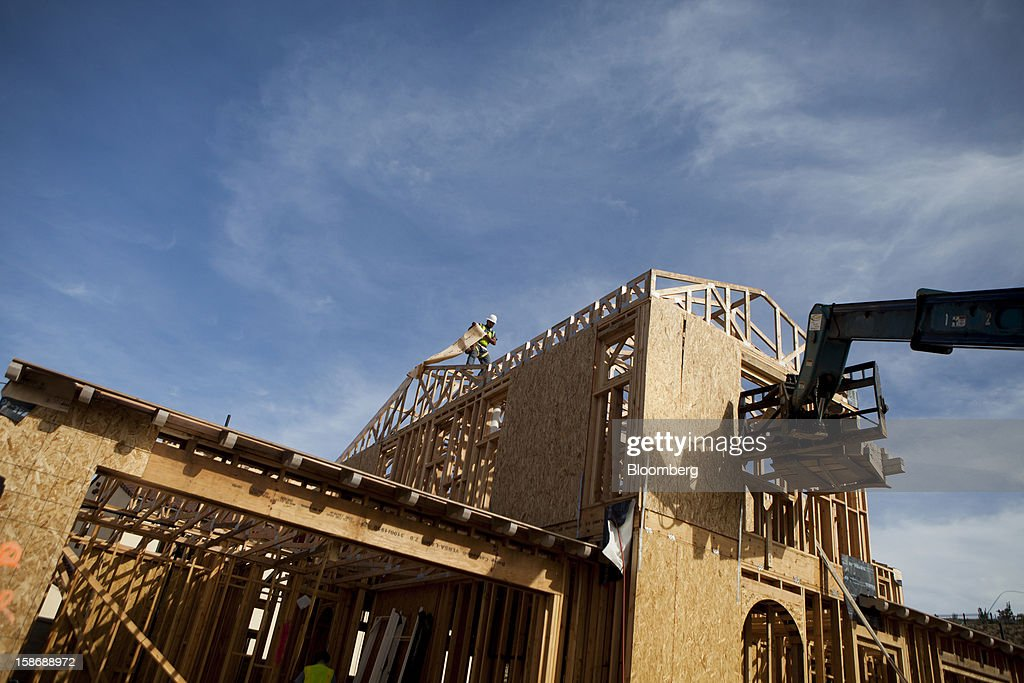 A worker installs material while standing on the roof of a house under construction at Davidson Communities LLC's Arista at The Crosby development in Rancho Santa Fe, California, U.S., on Friday, Dec. 21, 2012. New home sales climbed to a 380,000 annual rate in November, the most since April 2010, according to the median forecast of 60 economists surveyed by Bloomberg before Dec. 27 figures from the Commerce Department. Photographer: Sam Hodgson/Bloomberg via Getty Images