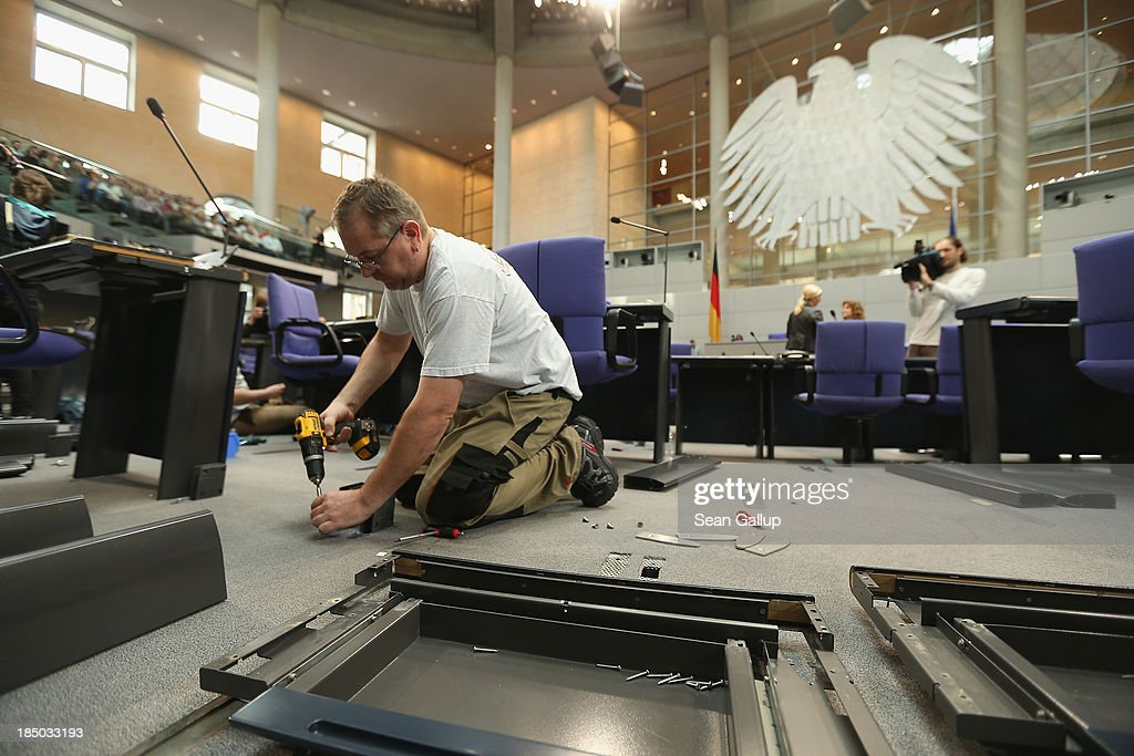 A worker installs new desks and chairs in the plenary hall of the Bundestag on October 17, 2013 in Berlin, Germany. Workers installed new chairs and rearranged seating in order to accomodate the new constellation of party factions as well as the slightly higher number of parliamentarians voted in for the 18th legislative period following recent German elections. The new Bundestag will convene for th first time on October 22.