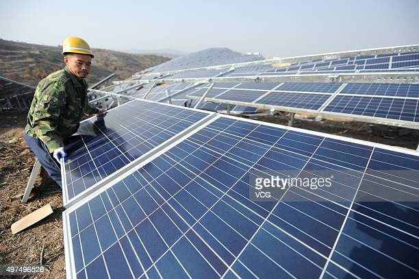 A worker installs polycrystalline silicon solar panels as terrestrial photovoltaic power project starts in Guanshui Town of Muping District on...